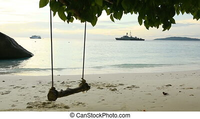 A rope swings on the beach at Similan island, Thailand, and...
