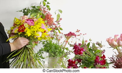 Florist prepares a bouquet of flowers for sale to customers...