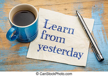 Learn from yesterday - handwriting on a napkin with a cup of...