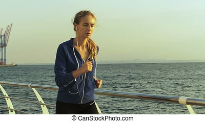 Adorable young blond woman listening to music, while running near the sea.