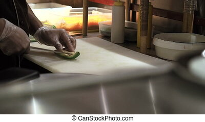 Process of making sushi rolls. Man cutting up green ripe avocado by slices. Prepared sushi rolls pass through on foreground