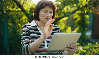 Cheerful Aged Woman connected by Skype - Cheerful Aged Woman...