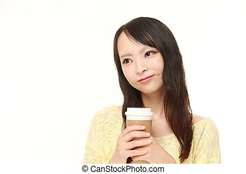 Japanese woman takes a coffee break - studio shot of young...