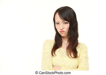 young Japanese woman in a bad mood - studio shot of young...
