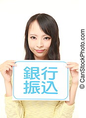 woman holding a message board with the phrase bank transfer...