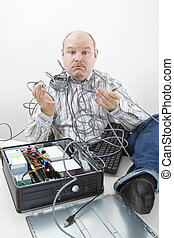 Confused Businessman Holding Tangled Cables Of Computer At...