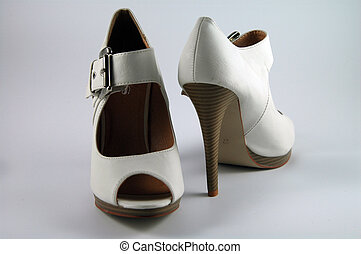 pair of creme-colored high heels with a buckle