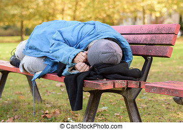 Homeless elderly woman sleeping rough in a park curled up...