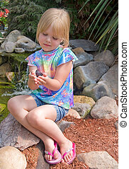 Handle With Care - Little girl holding a butterfly in a rock...
