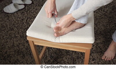 Woman cutting toenails - Woman cutting her toenails at home