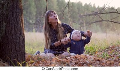 Mother with her baby boy in autumn forest falling leaves -...