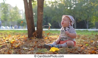 Baby in the forest. Falling autumn leaves. Slow Motion 100...