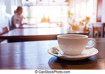 cup of coffee on table in cafe - White cup of coffee with...