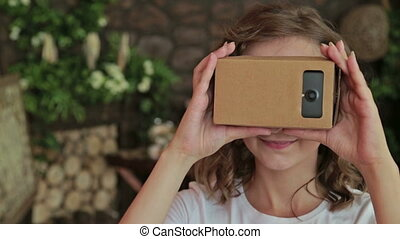 Young curly woman using Virtual Reality Glasses. Virtual...