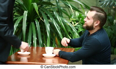 discussion in a coffee shop by two businessmen - discussion...