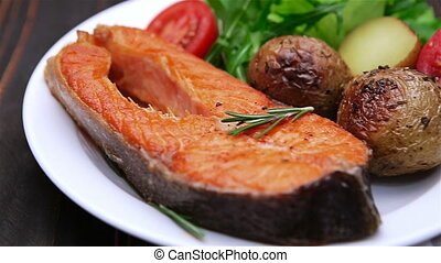 Crispy roasted salmon steak Isolated on wooden background