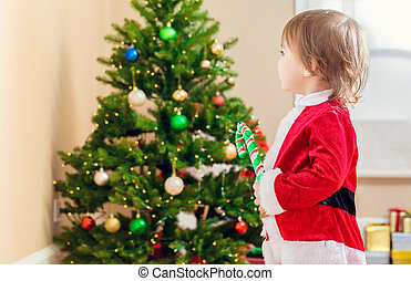 Toddler girl playing in front of the Christmas tree
