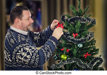 Mature man decorating Xmas tree - Standing sideways...