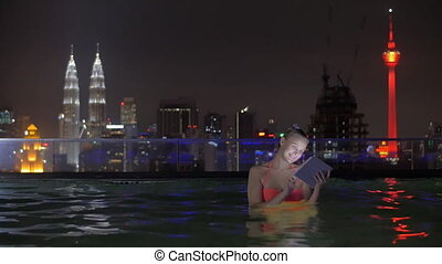 View of woman in swimming pool on the skyscraper roof using tablet against night city landscape. Kuala Lumpur, Malaysia