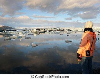 Woman admiring glacier lake - Young woman admiring...