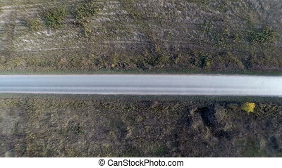 The white car goes on the road. Aerial view - fast Flight at...