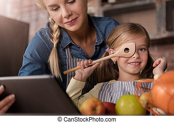 Joyful girl having fun with her mother in the kitchen - I...