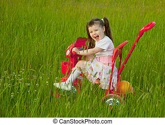 Cheerful little girl goes on a bicycle - The cheerful little...