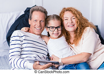 Delighted little girl hugging her grandparents - I love my...