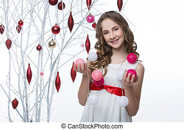 Beautiful girl standing near tree with christmas decorations