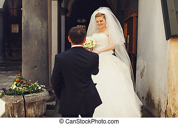 Groom helps charming bride to step out the door