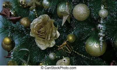 Golden decorations hanging on a Christmas tree.