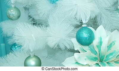 Christmas decorations hanging on white tree.