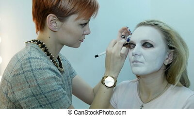 Professional make-up artist, using makeup to create a mask on Halloween. colors eye