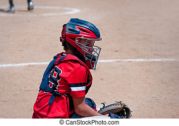Youth baseball catcher looking at coach. - American youth...