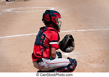 Youth baseball catcher behind home plate. - American youth...
