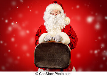 time christmastime - Santa Claus stands with old suitcase...