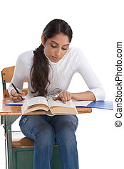 ethnic Indian college student by desk in class - English...