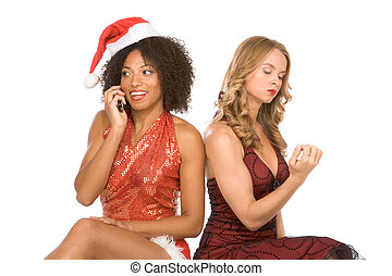 two Christmas women one talking on cell phone - Two lesbian...