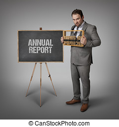 Annual report text on blackboard with businessman and abacus