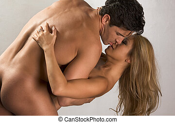 Naked mid aged interracial couple in love kissing -...