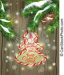 Winter holiday design. Old Wooden background with candy frame, fir tree branches and snow. Merry Christmas and Happy New Year calligraphy.