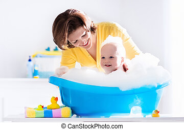 Young mother bathing baby boy - Happy baby taking a bath...