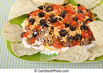 Taco Dip - Taco dip with tortilla chips on a plate