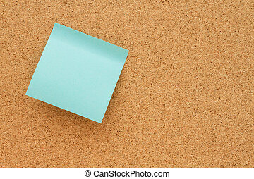 Bulletin board with a blank teal sticky note with copy space...