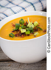 butternut squash soup topped with bacon and green onion on a...