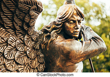 Statue Of Archangel Michael With Outstretched Wings Before Red Catholic Church Of St. Simon And St. Helena