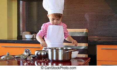 The small child in chef suit helps her mother cook in the kitchen