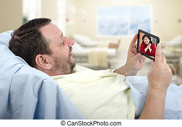 Man in hospital bed chatting - Bearded male patient lying on...