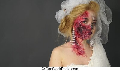 Playful blond woman disguised as a dead bride looks in the...