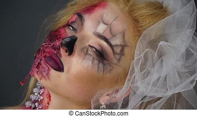 Dead bride with beautiful makeup for Halloween rolls his...